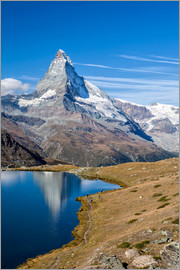 Roberto Moiola - Hikers walking on the path beside the Stellisee with the Matterhorn reflected. Zermatt Canton of Val