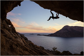 Climber in a cave at sunset