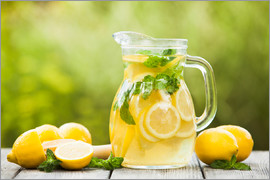 Lemonade in the jug and lemons with mint