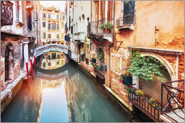 Traditional gondolas between colorful houses in Venice