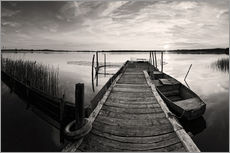 Wooden pier on lake with fishing boat - black and white