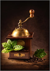 Coffee mill with beans and green leaves and a cup of coffee