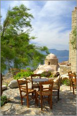 Tables and chairs on a terrace by the sea