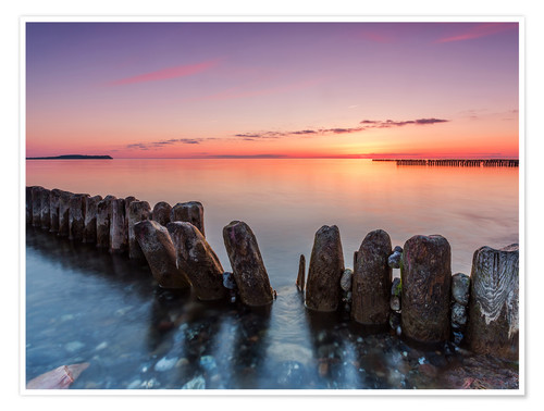 Premium poster Breakwater on the beach of the sea in the sunset