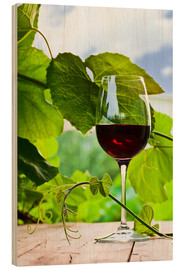 Wood print  glass with red wine in vineyard