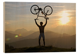 Wood print  Man holding a racing bike above his head - imageBROKER