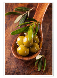 Poster Spoon with green olives on a wooden table